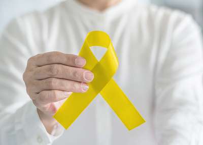 Person holding a yellow ribbon.